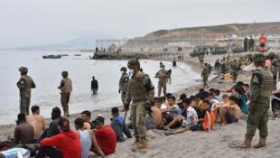 Migrantes, incluido menores, que llegaron nadando a Ceuta, junto a soldados del ejército español, el 18 de mayo de 2021