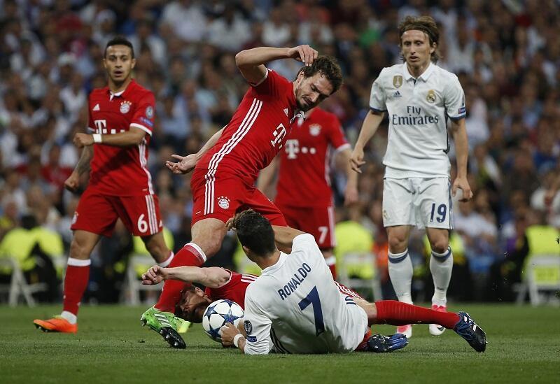 Dan wasan Real Madrid Cristiano Ronaldo yayin fafatawa da 'yan takwarorinsa ba Bayern Munich, Mats Hummels da Xabi Alonso a filin wasa ba Santiago Bernabeu da ke Madrid, ranar 18 ga watan Afrilu shekara ta 2017.