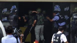 Des policiers tentent de sauver des otages lors d'affrontements à Hotan, au Xinjiang, le 18 juillet 2011.