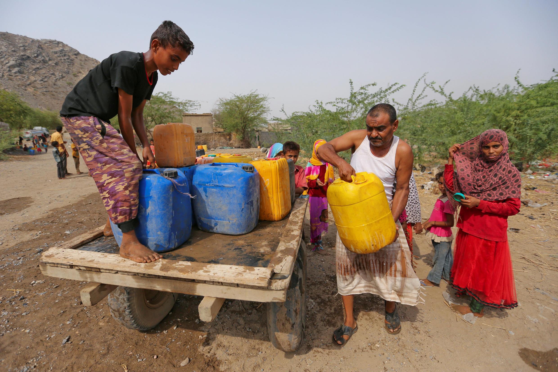 Habitantes  de Bajil, província iemenita de Hodeidah, recebem jerrycans com  água potável .29 de Julho  de 2017
