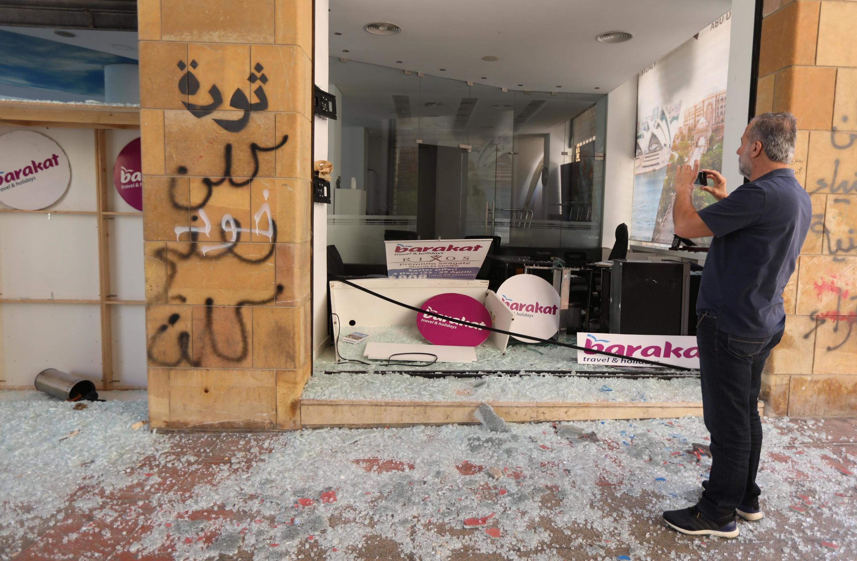 Un homme devant une agence de voyage saccagée après une nuit de manifestation à Beyrouth le 12 juin 2020.