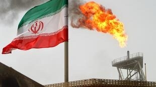 Gas flares from an oil production platform, as an Iranian flag is seen in the foreground, at the Soroush oil fields