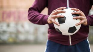 Image générique d'un homme tenant dans ses mains un ballon de football.