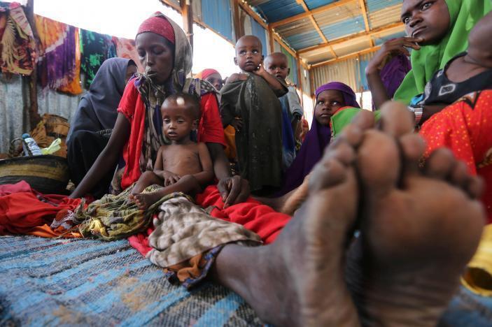 mwanamke wa kisomali aliyekosa makazi akiwa na watoto wake katika kambi ya  Al-cadaala Mogadishu.