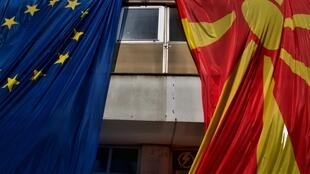 The Macedonian flag alongside the European Union flag on a building in Skopje.