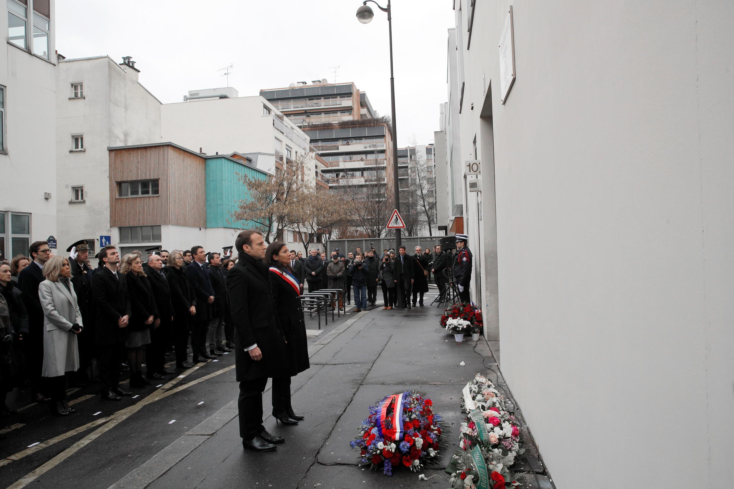 French President Emmanuel Macron (C) and Paris mayor Anne Hidalgo (rear C) observe a minute of silence outside the satirical newspaper Charlie Hebdo former office, to mark the third anniversary of the attack, in Paris, on January 7, 2018.