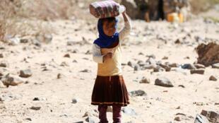 Una pequeña refugiada yemenita transporta un pote con agua, sobre su cabeza, hasta el campamento Marib. Sanaa, Yémen, 29 de marzo de 2018.