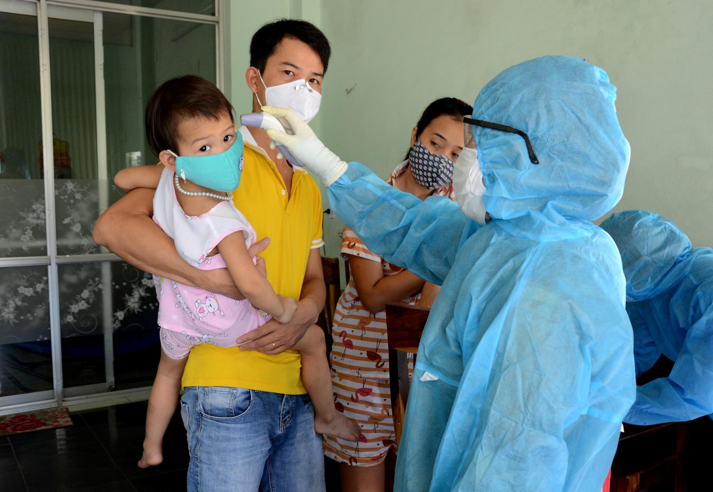 Nhân viên y tế kiểm tra thân nhiệt của cư dân trong một khu vực có bệnh nhân mới bị nhiễm Covid-19 tại thành phố Đà Nẵng, miền Trung Việt Nam. Ảnh chụp ngày 26/07/2020.