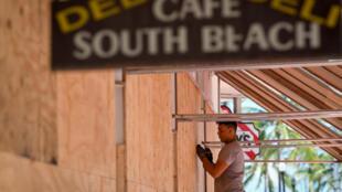 """Рабочий забивает окна ресторана фанерой в Майами-Бич, по которому должен ударить ураган """"Ирма"""", 7 сентября 2017 г."""