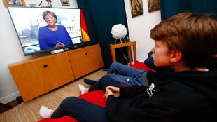 A German family watches Chancellor Angela Merkel's speech on television during the spread of coronavirus disease (COVID-19) in Berlin, Germany, March 18, 2020.
