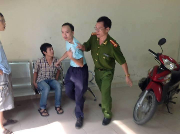 Sáng 15/08, các thanh niên nhóm học tiếng Anh đến trụ sở công an phường để đòi lại đồ dùng cá nhân. Trong ảnh, anh Hồ Ngọc Thanh bị một nhân viên công an lôi đi.