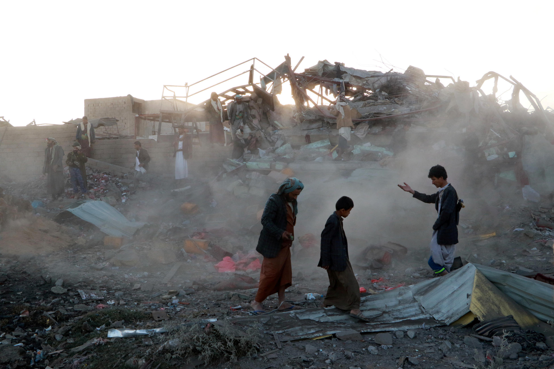 As pessoas caminham no local de um ataque aéreo na cidade noroeste de Sanaa, no Iémen.