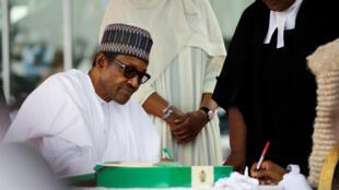 Shugaba Muhammadu Buhari na sa hannu kan wata takarda bayan ya yi rantsuwar kama aiki