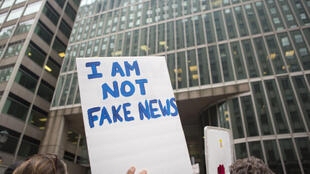"""Manifestante ergue cartaz que diz """"Eu sou não sou uma 'notícia falsa'"""""""