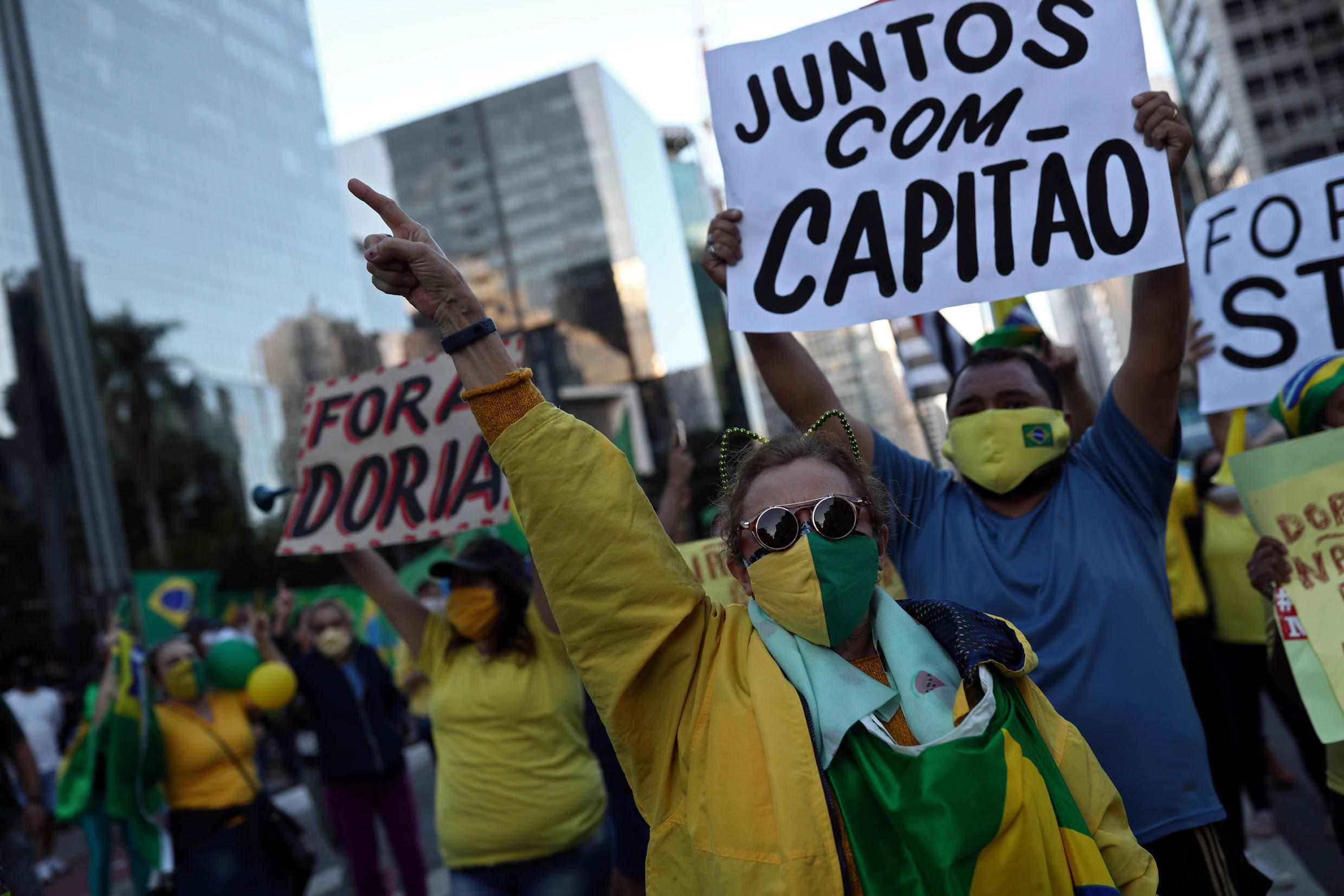 """Supporters of far-right Brazilian President Jair Bolsonaro take part in a protest against social distancing and quarantine measures, recommended by Sao Paulo's governor Joao Doria, following the coronavirus disease (COVID-19) outbreak, in Sao Paulo, Brazil, May 3, 2020. The placard reads: """"Together with the captain."""""""