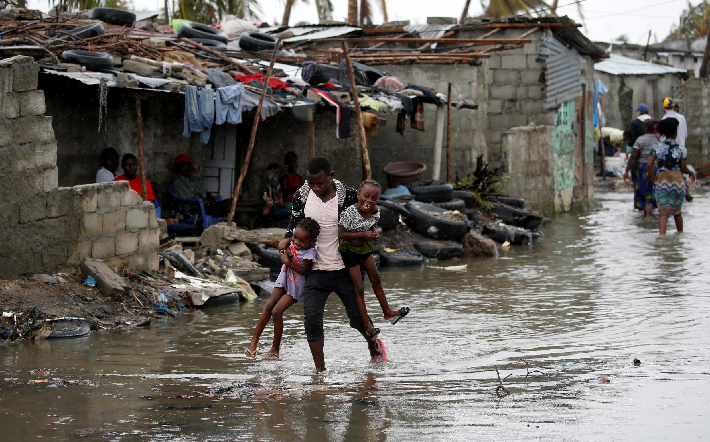 Un homme porte ses deux enfants dans Beira inondée, le 23 mars 2019.