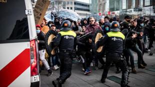 Enfrentamientos con la policía al margen de las manifestaciones contra el toque de queda para contener el avance del coronavirus, en Eindhoven, Holanda, el 24 de enero de 2021