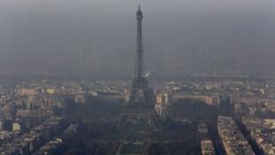 Nuvem de poluição impede a visão nítida da Torre Eiffel.