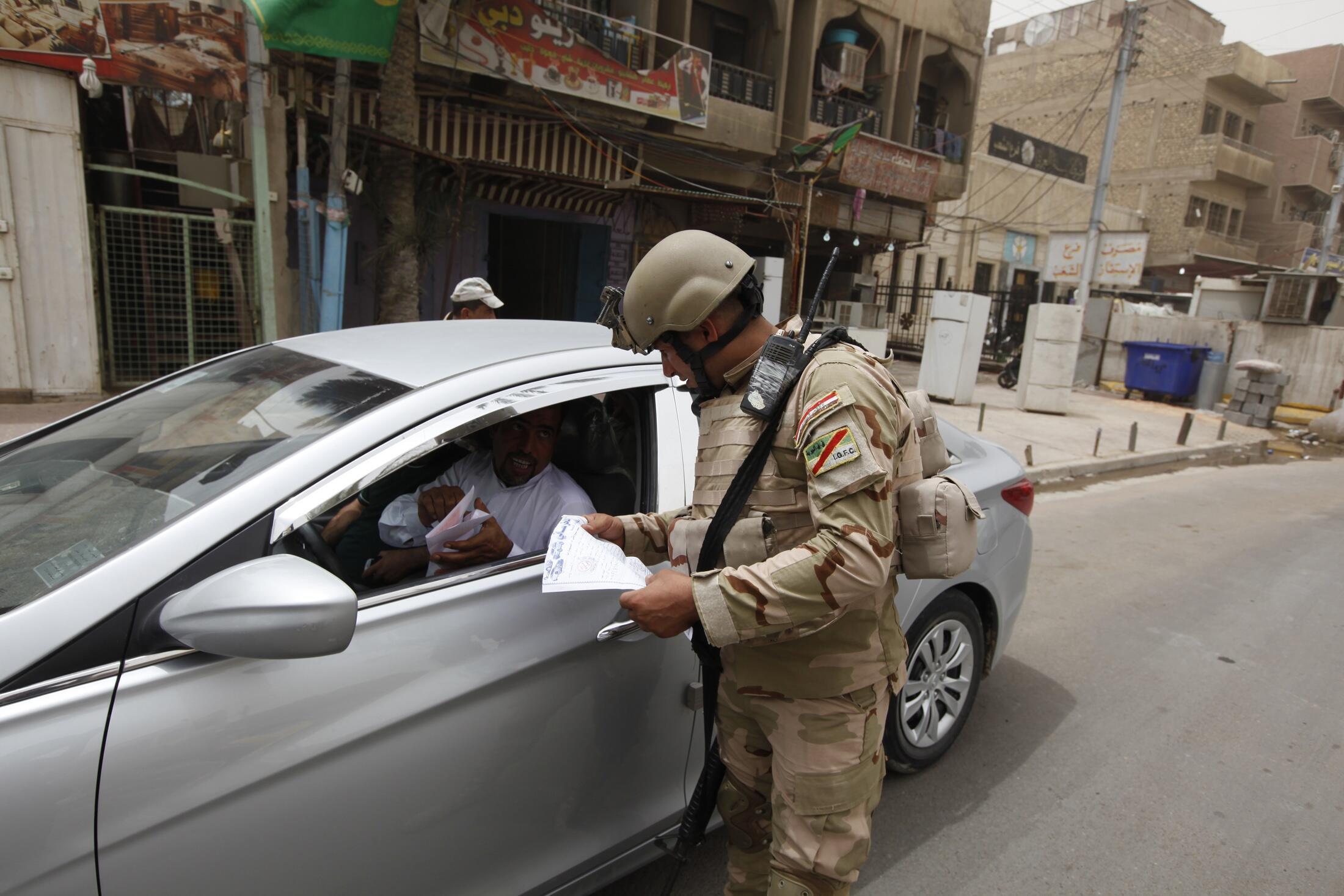 Un soldat irakien contrôle un véhicule dans Bagdad le 11 juin 2014 à un barrage routier.