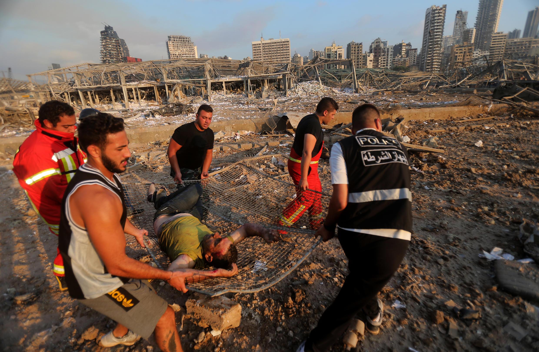 Feridos são retirados dos escombros após as duas explosões no porto de Beirute na terça-feira (4).