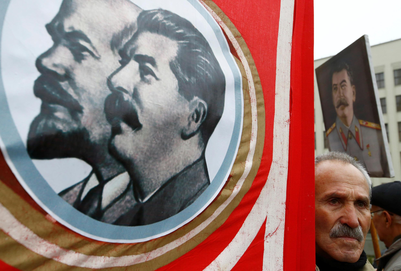 Мужчина с портретами Ленина и Сталина на площади Независимости в Минске, 7 ноября 2018