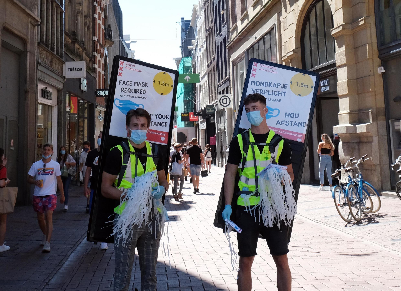 Dans les rues d'Amsterdam, les mesures anti-coronavirus sont prônées.