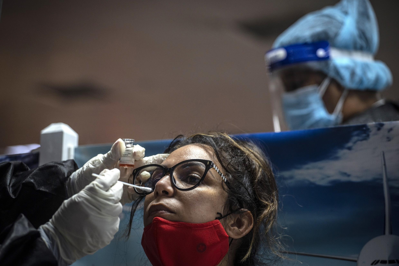 Une jeune femme se fait tester au Covid-19 à son arrivée à l'aéroport international de la Havane, le 15 novembre 2020.
