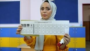 A woman shows a ballot paper at a polling station during a mayoral election re-run in Istanbul, Turkey,23 June, 2019.