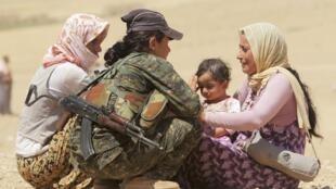 Image d'archive: menacés par les jihadistes, des Yézidis fuient la ville de Sinjar, dans le nord de l'Irak, aidés par les forces de défense populaire kurdes (YPG), en août 2014.