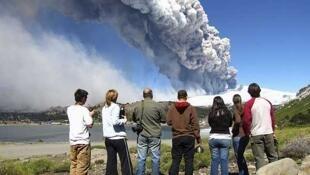 Residentes de la localidad argentina de Caviahue, a 10 Kilómetros del volcán, observan la columna de humo.