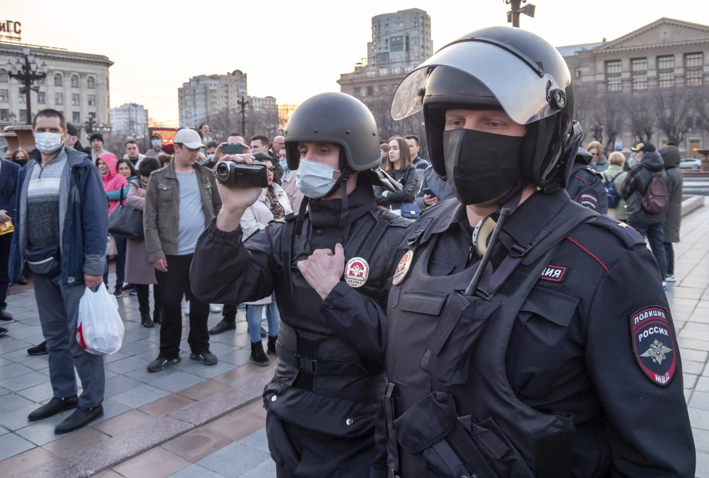 A Russian police officer films people ahead of the possible opposition rally in support of jailed opposition leader Alexei Navalny in Khabarovsk, 6,100 kilometers (3,800 miles) east of Moscow, Russia, Wednesday, April 21, 2021. Navalny's team has called for nationwide protests on Wednesday following reports that the politician's health was deteriorating in prison, where he has been on hunger strike since March 31. Russian authorities have stressed that the demonstrations were not authorized and warned against participating in them. (AP Photo/Igor Volkov)