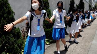 Les élèves du secondaire forment une chaîne humaine contre le projet de loi sur l'extradition à Hong Kong, en Chine, le 3 septembre 2019.