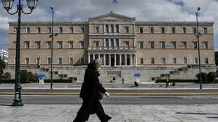 A woman wearing a face mask walks past the empty Syntagma Square in Athens, in front of the Greek Parliament early during the outbreak of COVID-91.