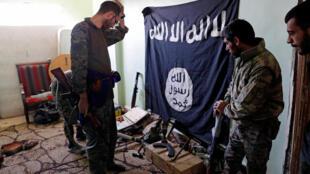 Integrantes das Forças Democráticas Sírias (FDS) inspecionam armas e munições apreendidas de combatentes do grupo Estado Islâmico em Raqa.