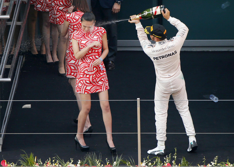 Lewis Hamilton molha grid girls com champanha para celebrar vitória em Xangai, em 2015.