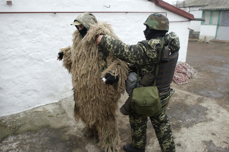 Un soldat ukrainien aide son camarade à enfiler sa tenue de camouflage, dans un village près de Marioupol, le 26 janvier 2015.