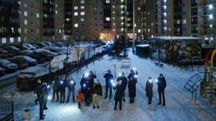 Những người ủng hộ nhà đối lập Alexei Navalny bật đèn điện thoại di động, chụp ảnh chung tại một khu nhà ở ngoại ô Saint Petersburg, Nga, nhân Ngày Valentin (Lễ Tình Yêu), 14/02/2021.