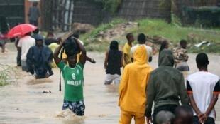 Os habitantes caminham sobre uma estrada inundada, após a passagem do ciclone Kenneth em Pemba, 28 de Abril 2019.