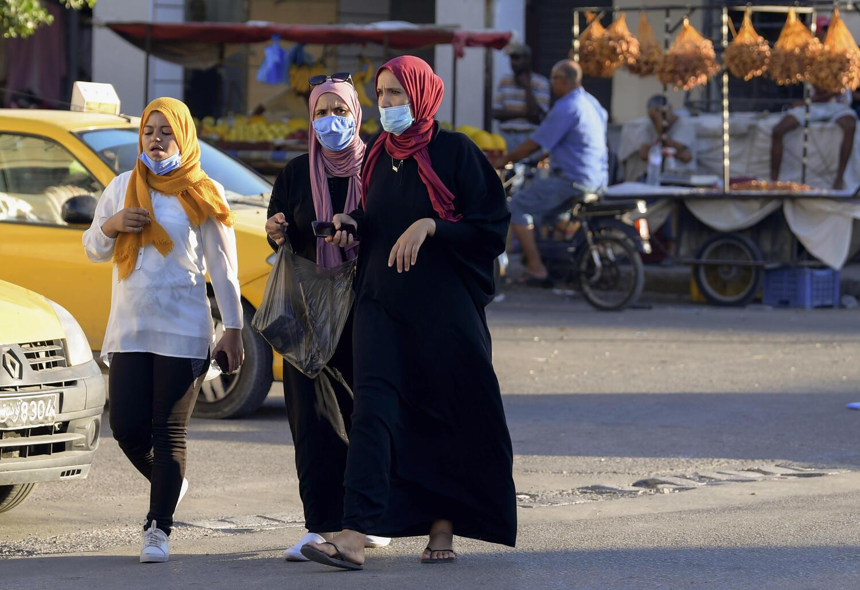 Des Tunisiennes marchant dans la rue et portant un masque pour se protéger du Covid-19, le 26 août 2020 à Gabes.