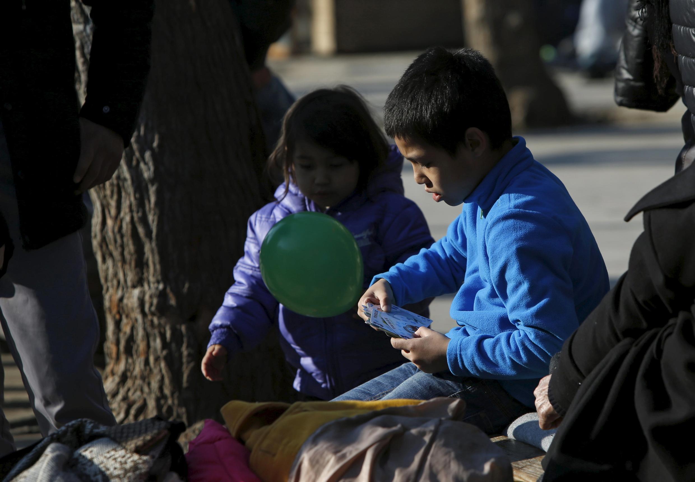 Des enfants migrants jouent place Victoria, à Athènes, le 27 janvier 2016.