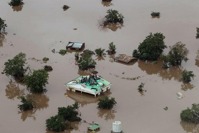 This handout picture taken and released on March 18, 2019, by the Mission Aviation Fellowship shows people on a roof surrounded by flooding in an area affected by Cyclone Idai in Beira.