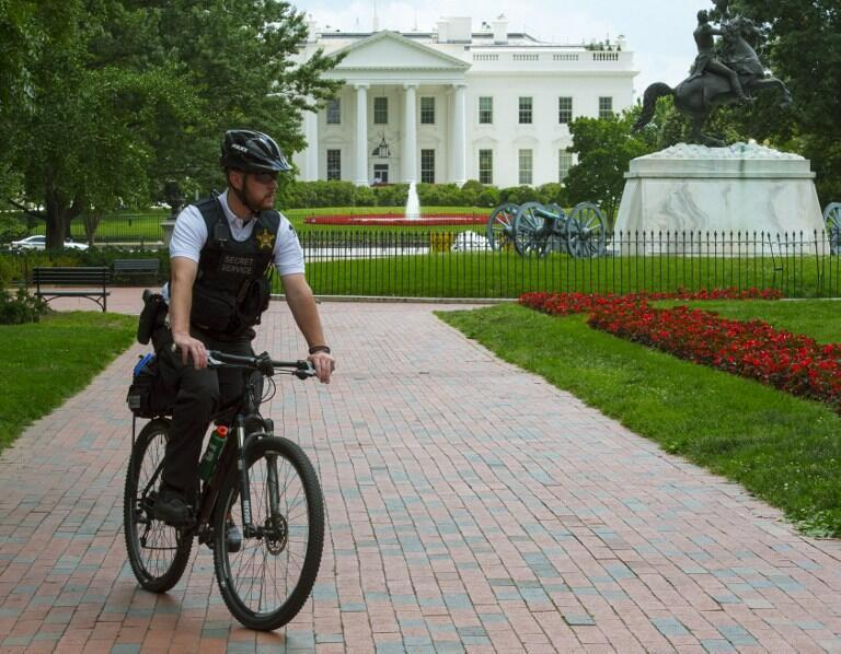 Un membre des Services secrets patrouille devant la petite grille d'enceinte de la Maison Blanche, à Washington, le 9 juin 2015.