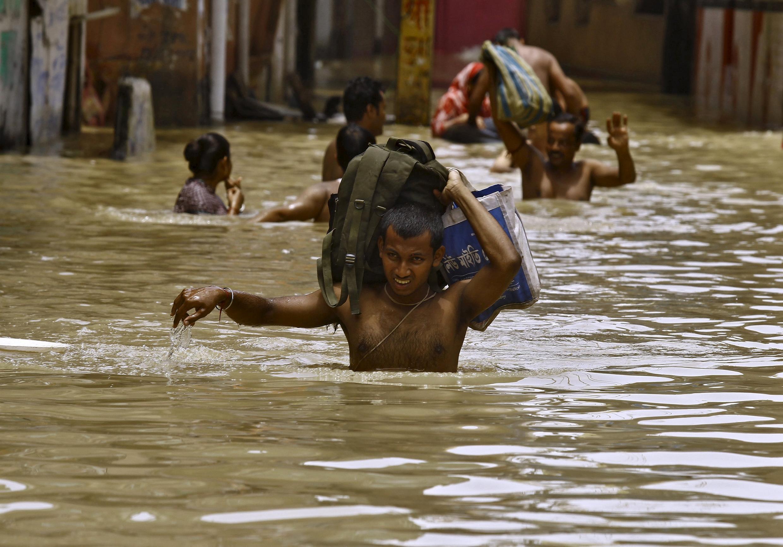 Indianos carregam seus pertences em meio a enchente, em agosto deste ano