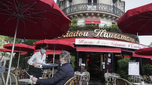 A customer is served at a cafe in Paris on May 19, 2021.