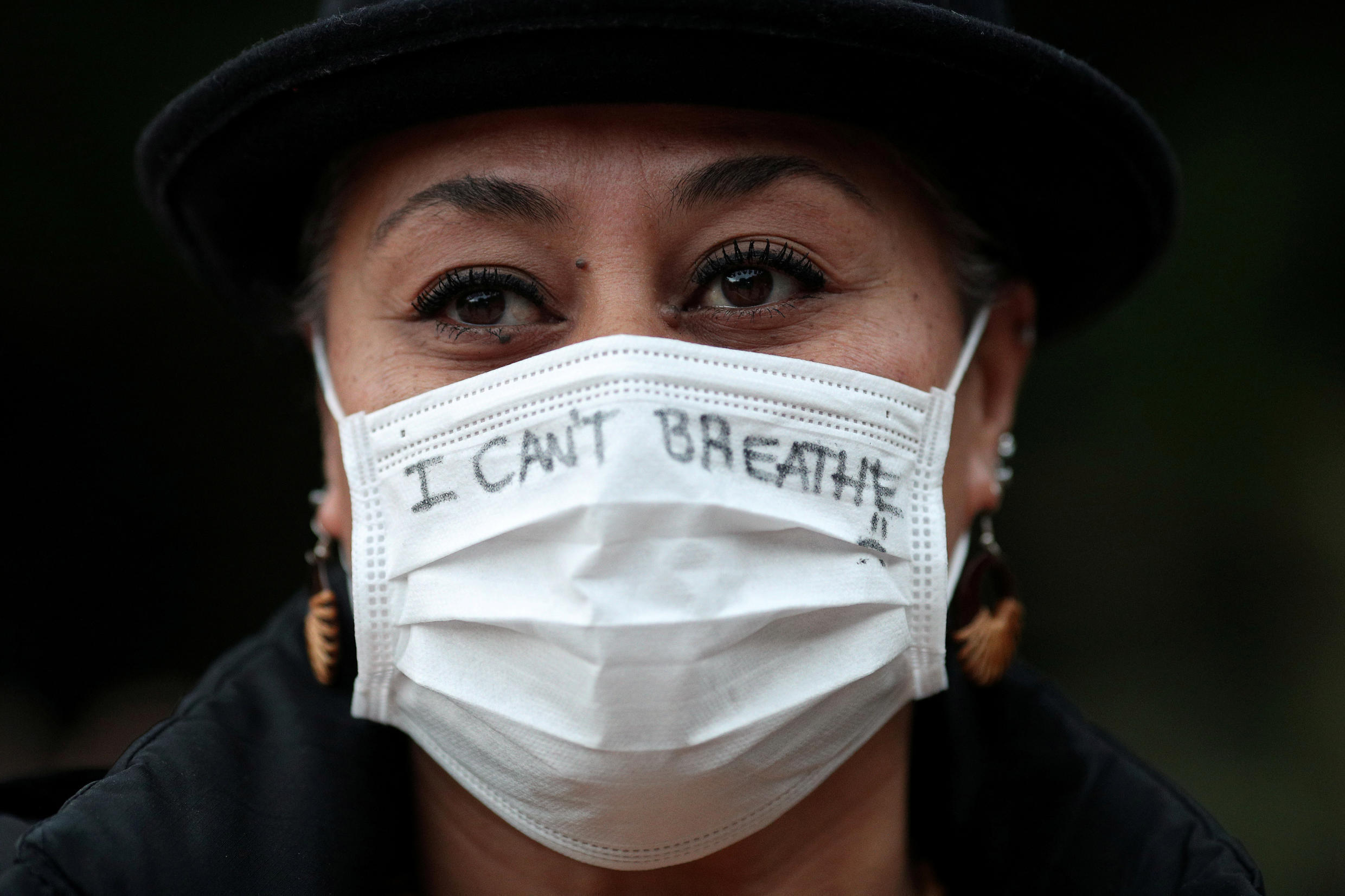 FILE PHOTO: A woman wears a face mask as people protest in solidarity with those in the United States protesting police brutality and the death in Minneapolis police custody of George Floyd, in Sydney, Australia, June 2, 2020.