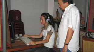 Le réalisateur Rithy Panh, auteur du document S21, la machine de mort Khmer rouge, aux côtés d'une étudiante consultant les archives au Centre d'archives audiovisuelles Bophana, à Phnom Penh.