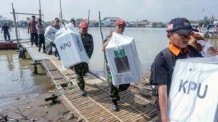 Les officiels transportent le matériel électoral devant être distribué à Pekalongan, dans la province de Java central, en Indonésie, le 16 avril 2019.