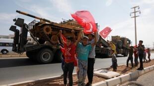 土耳其坦克向叙利亚边境挺进,一些年轻人举着土耳其国旗欢呼。