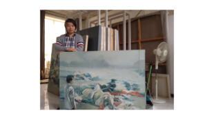 Chen Guang dans son atelier à Pékin, derrière son autoportrait. Soldat en 1989, l'artiste avait reçu l'ordre de prendre la place Tian'anmen en photo - au lendemain du massacre.