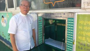 """Le pasteur Lee Jong-rak montre la """"boîte à bébés"""" qu'il a installée devant son église dans le sud de Séoul. Elle permet aux mères désespérées de déposer leur bébé anonymement."""